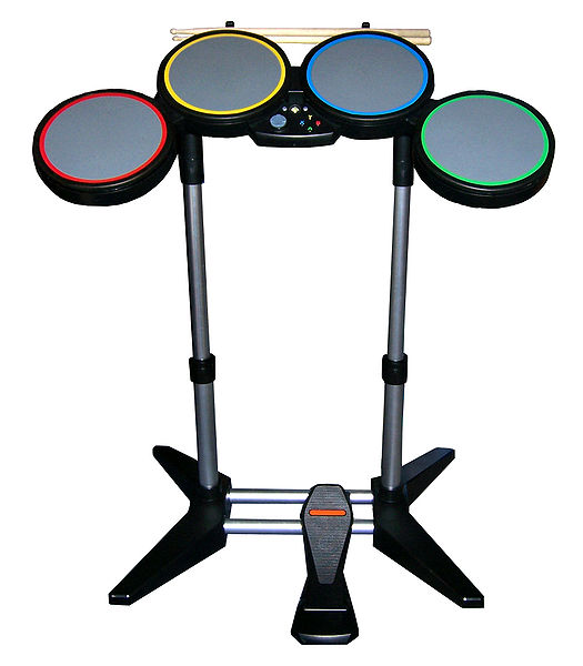 The drum controller, which features 4 pads, a bass drum pedal, and real drumsticks. The Wii version features white drums.